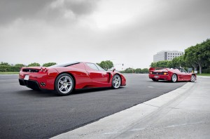 Two ferraris coming off a stretch of road