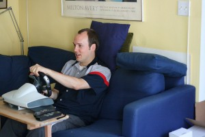 in action photo of a video gamer playing a racing game using a wheel and pedals controller set up