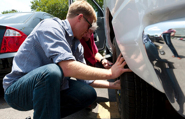Two motorists lent down changing a car tyre on a sunny day.