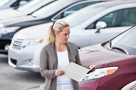 Photo of woman browsing new cars